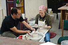 An instructor and studen work to create a clay pot