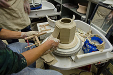 A picture of a caly pot with a piece being carved away