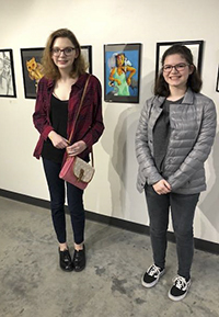 students standing in front of artwork